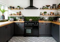 Cocina integral negra con instrumentos colgados en la pared